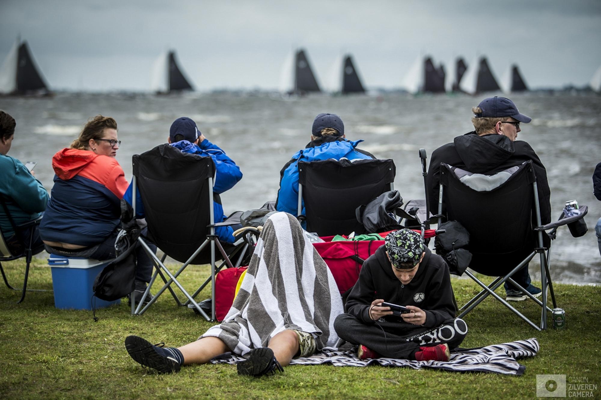 TERHERNE - Publiek langs het water bij Terherne tijdens de vierde wedstrijd van het traditionele skutsjesilen. Twee weken lang strijden 14 traditionele Friese platbodems tegen elkaar op de meren van Friesland.