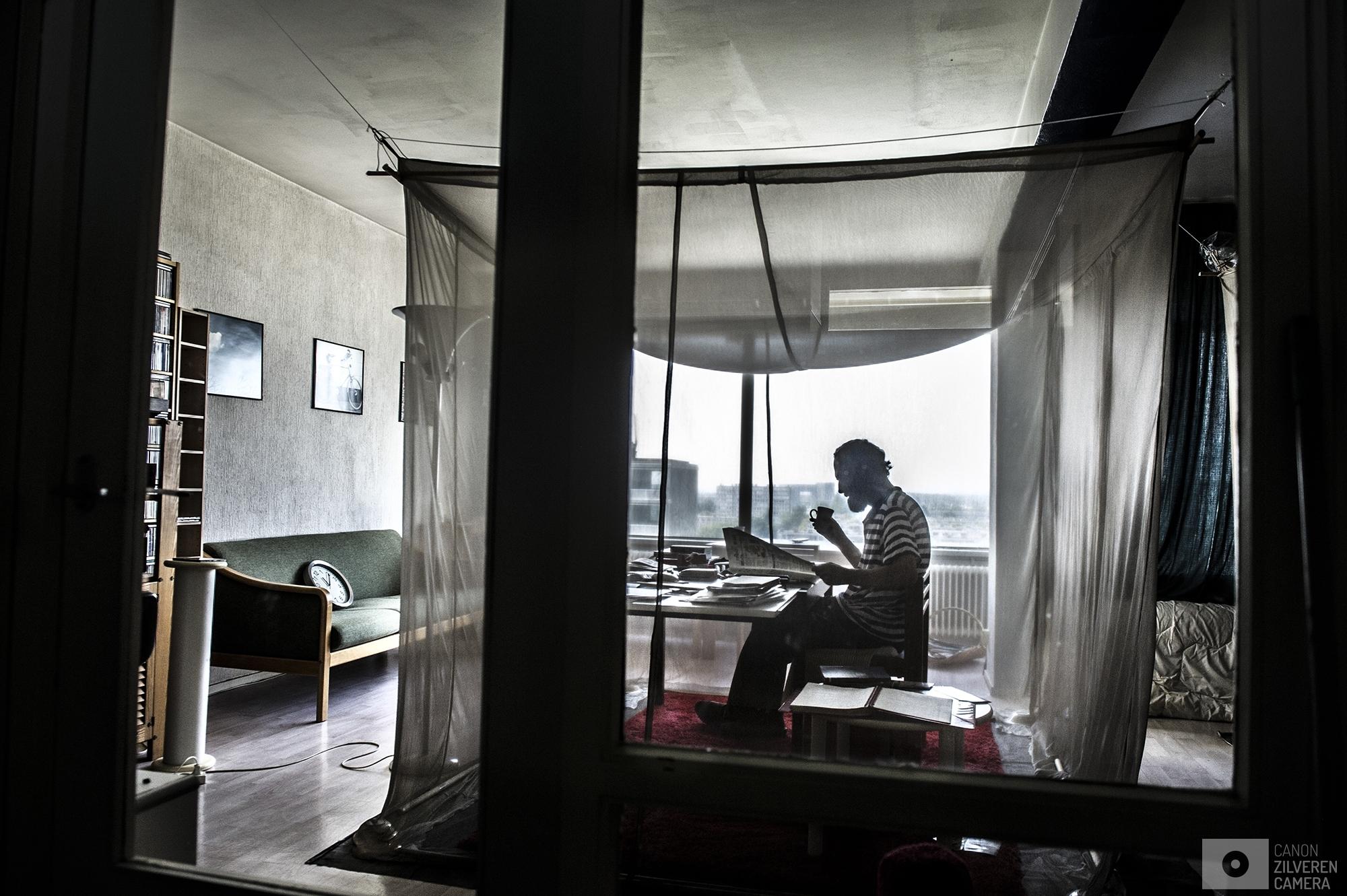 Nederland,Utrecht,29-08-2017leven met EHS   numr 1Nederland,Utrecht,29-08-2017 Henk de Moei , woont op 10 hoog tegen het centrum van Utrecht aan , zins 2005 heeft Henk in zijn woonkamer twee klamboe's met zilverdraad hangen een om in te slapen en een om in te leven. Deze werken als een kooi van faraday (Faraday' gebruikt voor ruimtes die elektromagnetische straling buitensluiten: elektromagnetisch dode ruimtes) In 2005 kreeg Henk veel last van vermoeidheid slapeloosheid en nog veel meer onverklaarbare klachten. Na veel zoeken kwam Henk tot de conclusie dat de UMTS masten op het dak van de flat waar hij woont de oorzaak moet zijn. Als Henk nu thuis is dan zit hij nu in zijn zilveren kooi beschermt tegen de Hoogfrequente elektromagnetische straling van de umts masten. Toen er spraken was dat er een umts mast op het dak van de flat zou komen heeft hij zijn protest laten horen maar dit haalde weinig tot niks uit , omdat de service  kosten van de flat voor iedereen omlaag zouden gaan als de mast wel op het dak zou komen.Henk is erg boos en verdrietig en gefrustreerd geweest. Maar hij heeft zich bij deze oplossing neergelegd. Maar het kost hem heel veel geld op alle aanpassingen te doen. Hij heeft al meerde klamboes versleten die elk zo/n 2000,- euro kosten.Ook ligt er een speciaal doek die de straling tegenhoud op de grond.  verhuizen zou voor hem een hoop oplossen doet hij dat toch liever niet , nu zit hij 5 min lopen van het centrum van Utrecht en op het stadion staat hij dus ook zo. Henk kan uren door brengen in zijn zilveren kooi. Hij zet dan zijn tape recorder aan en dan kan  hij 2 x 90 minuten tot dat bandje twee kanten heeft gehad ongemoeid lezen. Iets met een antenne of straling zul je niet bij Henk vinden  om de zoveel dagen gaat hij naar de bibliotheek om zijn mail te bekijken.