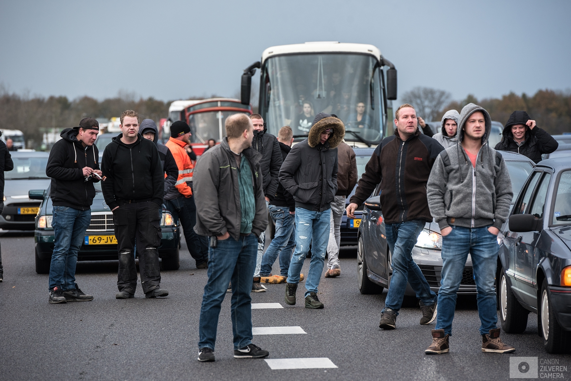 OUDEHASKE | The majority of men responsible for stopping the busses from heading towards dokkum are standing next to their cars and interacting with the media present.| #5
