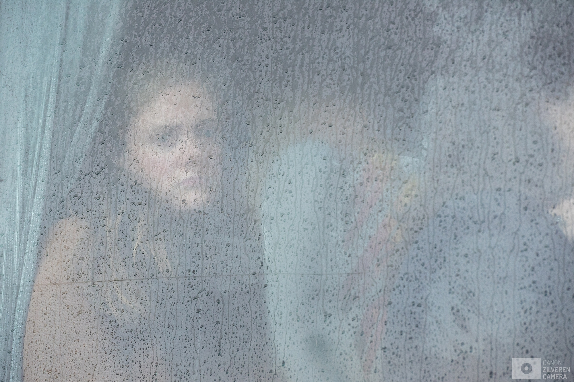 OUDEHASKE | A young woman is looking towards the camera from inside of one of the stopped busses.| #9