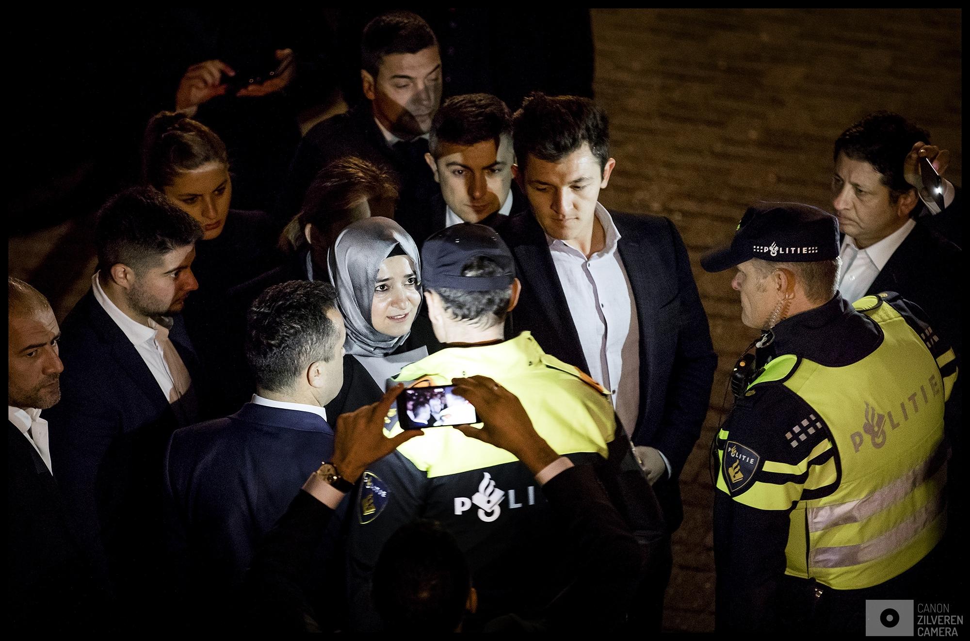 ROTTERDAM - De politie houdt de Turkse minister Fatma Betul Sayan Kaya van Familiezaken tegen als ze een poging doet om van haar auto naar het consulaat in Rotterdam te lopen. Aan de voorkant staat een woedende menigte van Turks Nederlandse Erdogan-aanhangers die ze wil toespreken.