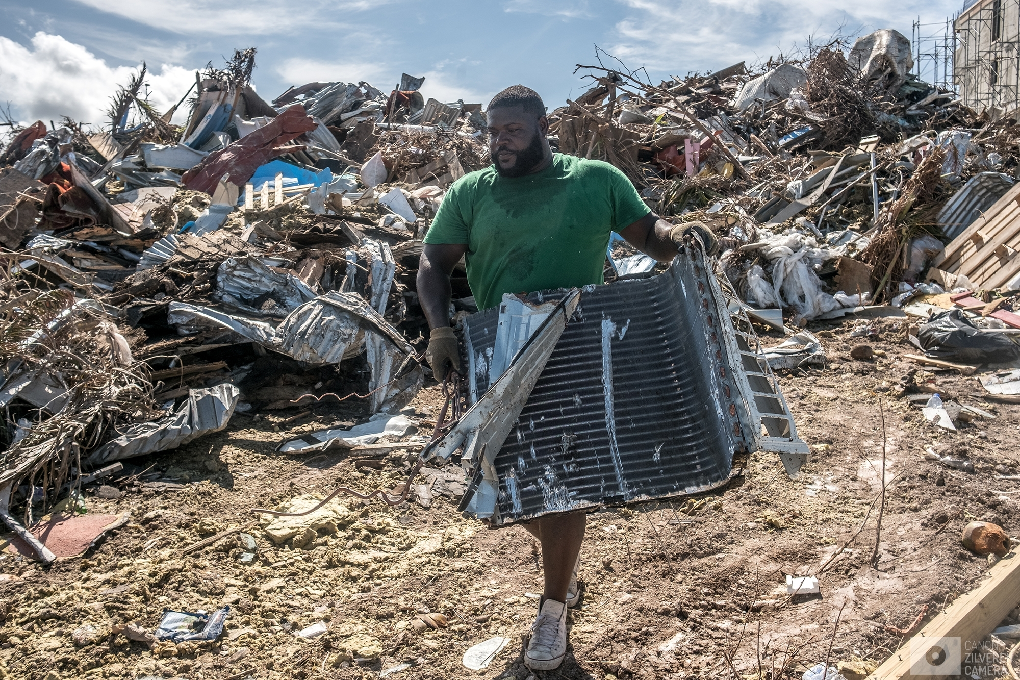 SINT MAARTEN | A man is collecting recycable parts from a landfill full of lefovers from damaged buildings. | #5