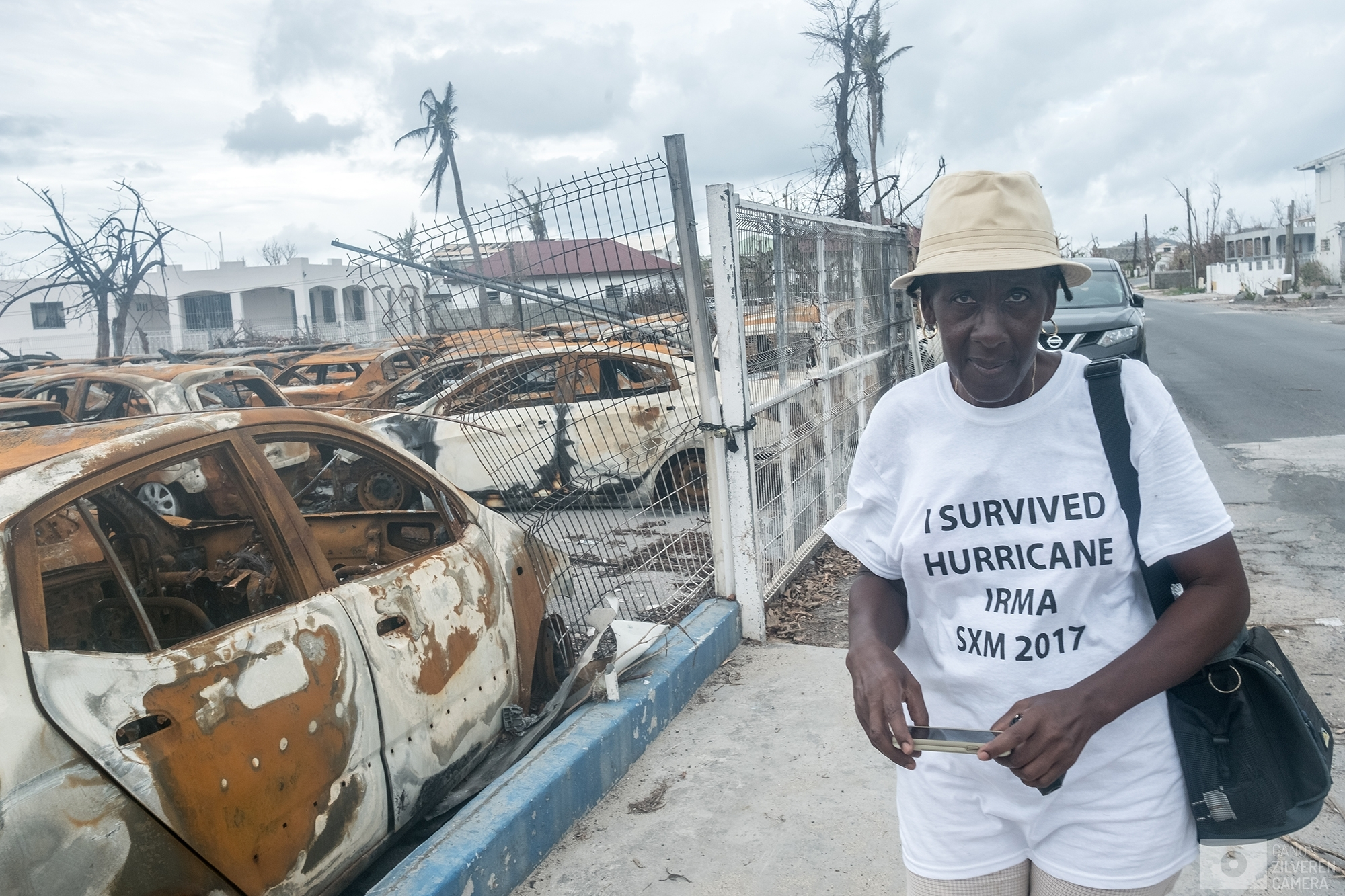 "SINT MAARTEN | A woman wearing a shirt saying ""I survived hurricane Irma SMX 2017"" is taking pictures of a graveyard for cars.