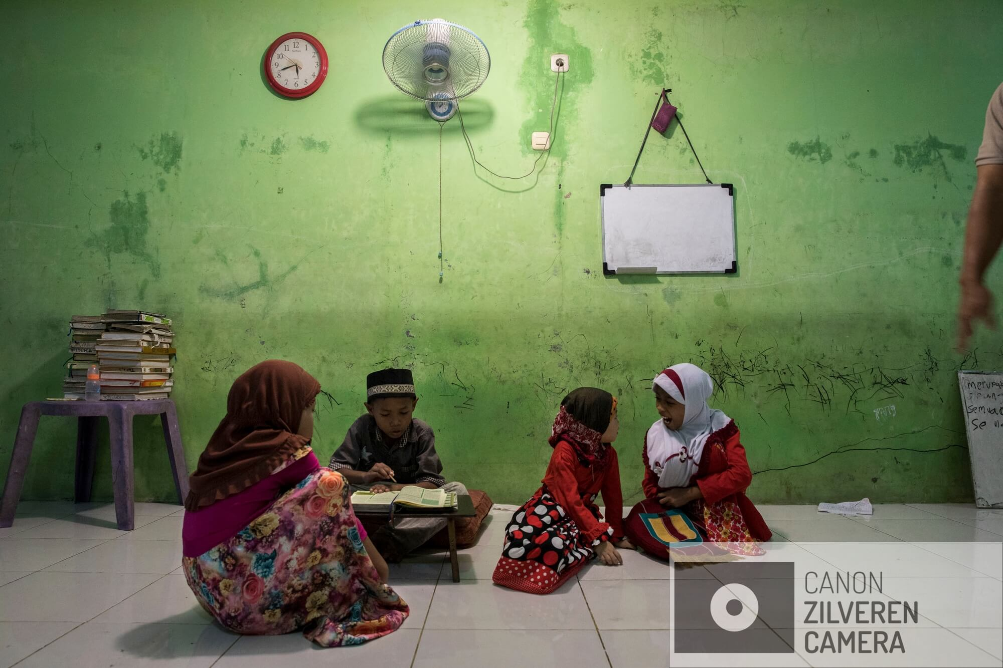 Jakarta zinkt snel, tussen 10-25 centimeter per jaar. Wanneer niets wordt gedaan zal de stad over 20-3- jaar voor een derde permanent onder water staan. Veel water gerelateerde problemen worden toegeschreven aan klimaatverandering en de verwachte zeespiegelstijging die daarmee samenhangt. Bodemdaling is onbekend en zal de absolute zeespiegelstijging tot een factor 10 overschrijden. Jakarta vertrouwd op een oude zeewering om de stad te beschermen tegen zee. Echter door bodemdaling zinkt deze muur snel weg in de grond en biedt weinig bescherming tegen het water. Zware regenval en een hoge rivierwater stand zorgen nu al voor problemen: de stad is veranderd in een omgekeerd aquarium. De zee is niet meer het laagste punt, het water kan nergens meer heen.De waterlijn in de Koran school in Muara Baru is een stille getuige van de laatste overstroming. Serie gemaakt tussen 2015 en 2018