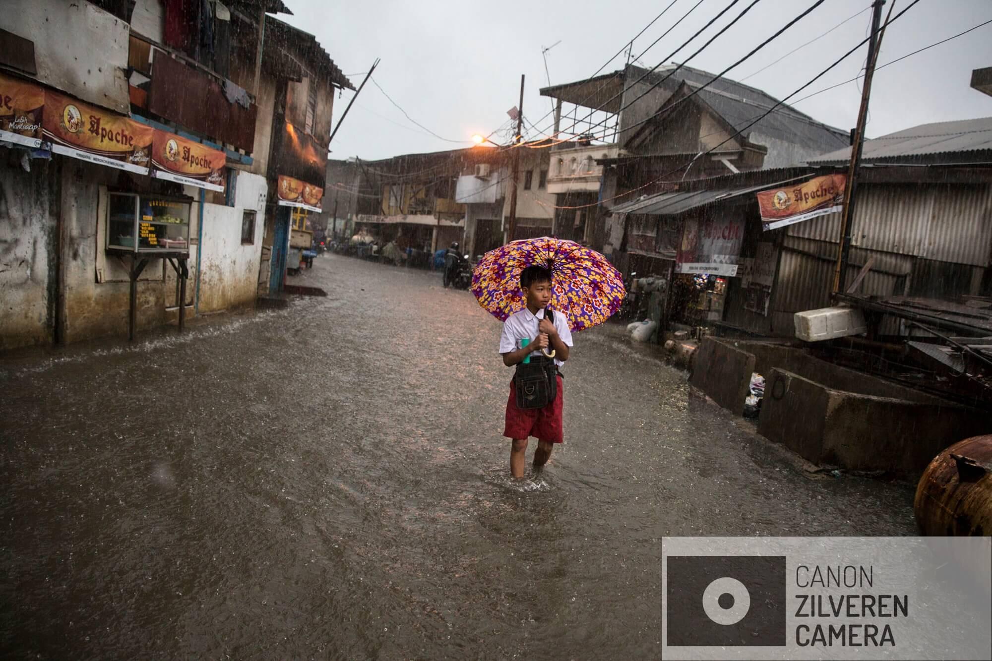Jakarta zinkt snel, tussen 10-25 centimeter per jaar. Wanneer niets wordt gedaan zal de stad over 20-3- jaar voor een derde permanent onder water staan. Veel water gerelateerde problemen worden toegeschreven aan klimaatverandering en de verwachte zeespiegelstijging die daarmee samenhangt. Bodemdaling is onbekend en zal de absolute zeespiegelstijging tot een factor 10 overschrijden. Jakarta vertrouwd op een oude zeewering om de stad te beschermen tegen zee. Echter door bodemdaling zinkt deze muur snel weg in de grond en biedt weinig bescherming tegen het water. Zware regenval en een hoge rivierwater stand zorgen nu al voor problemen: de stad is veranderd in een omgekeerd aquarium. De zee is niet meer het laagste punt, het water kan nergens meer heen.De hoofdstraat in Muara Baru, de wijk naast de zeewering staat vaak onder water. Het is een van de snelst dalende delen van de stad, het water stroomt erin maar er niet meer uit. Serie gemaakt tussen 2015 en 2018