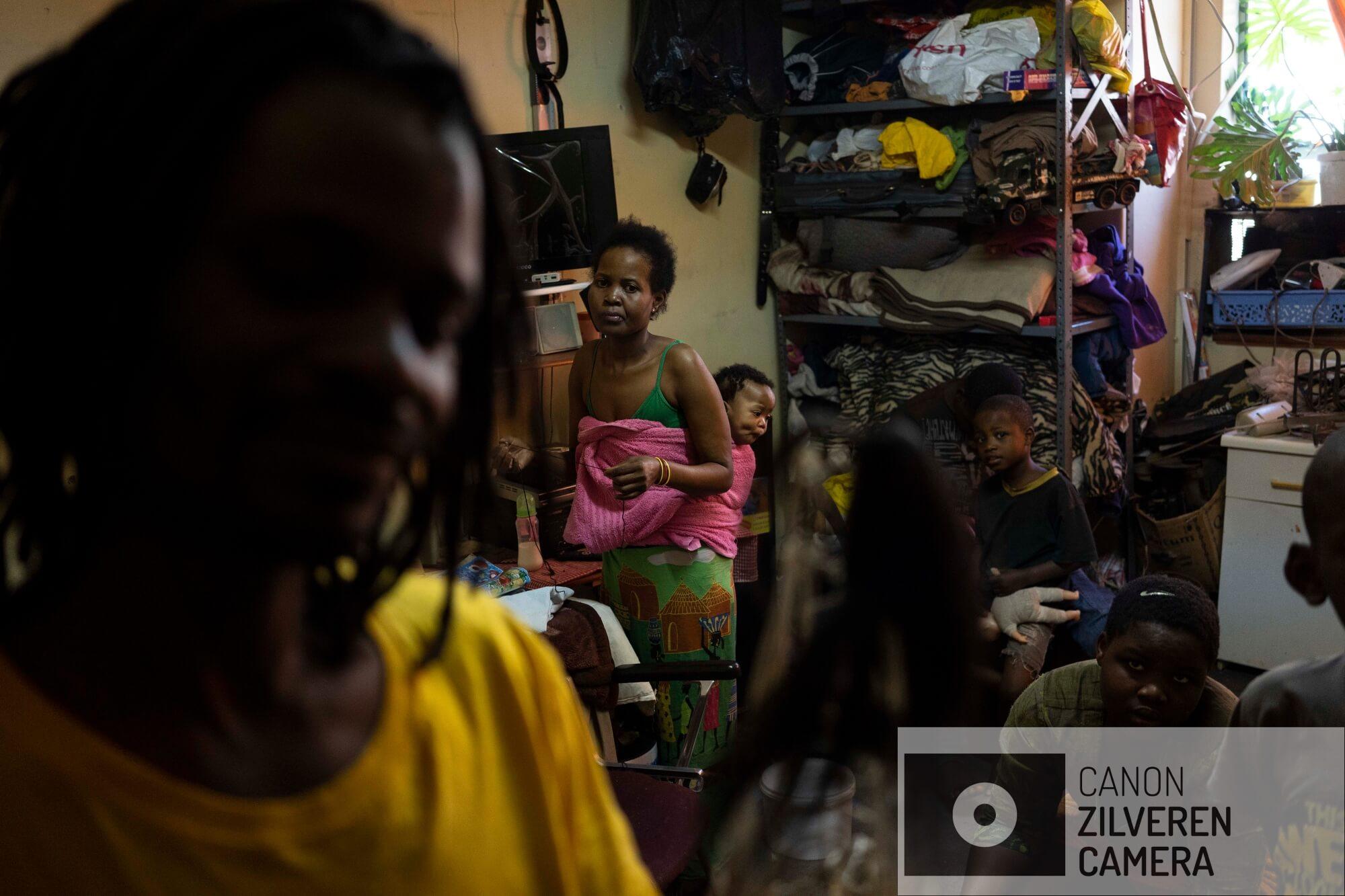De Zimbabwaanse migrant Kholakele draagt haar 6 maanden oude baby in haar appartement in downtown Johannesburg. Kholakele en haar man Arnold (links) zijn drie jaar geleden illegaal Zuid-Afrika binnen gekomen in de hoop werk te vinden. Ze kennen de verhalen van vermiste migranten via vrienden en familie en vrezen voor de levens van hun kinderen in het gewelddadige Johannesburg. 'Als een van hen langer dan 10 minuten wegblijft, bellen we ze', zegt Kholakele.