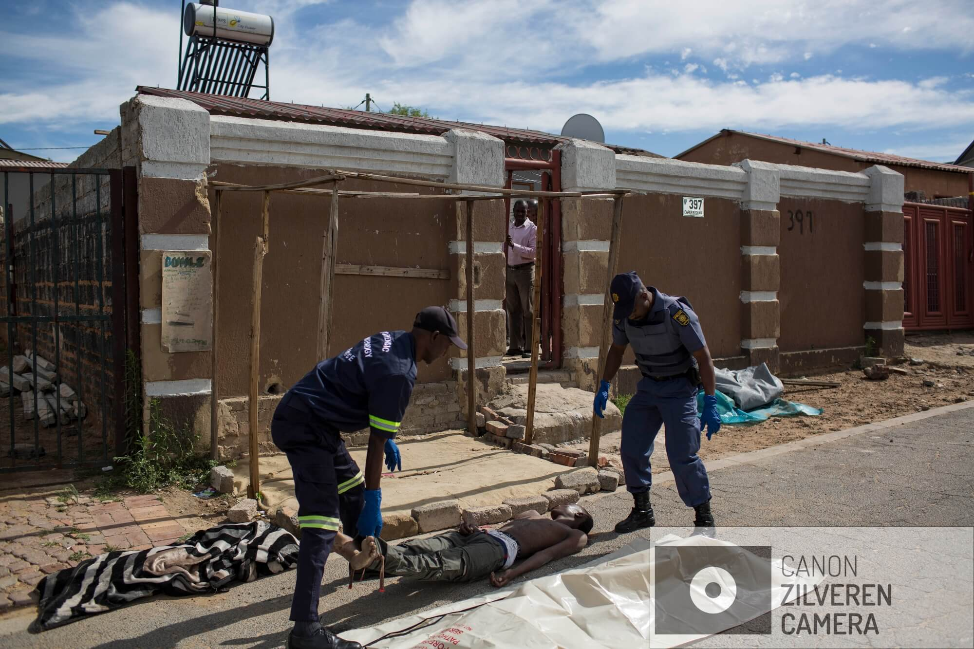 Het lichaam van een man vermoord in de wijk Alexandra in Johannesburg, wordt opgehaald door een medewerker van het mortuarium in Johannesburg. Van de 3.000 lichamen die worden binnengebracht, blijft ongeveer tien procent ongeïdentificeerd.