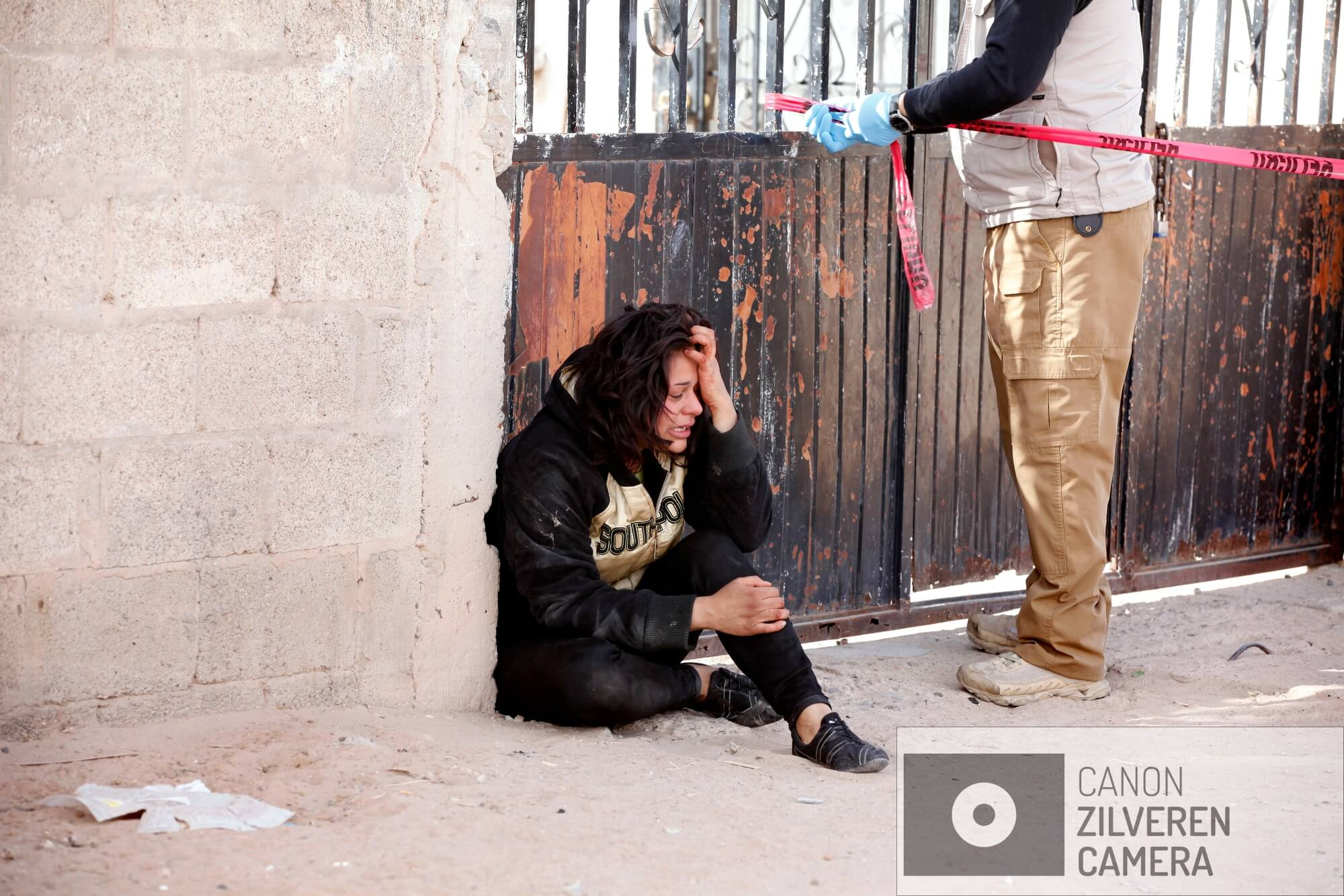 De 23-jarige echtgenote Lesly in tranen voor het huis van haar man Luis Ángel Rodriguez Contreras (27) die recht voor haar neus in huis werd doorzeefd met kogels door drie gemaskerde mannen.