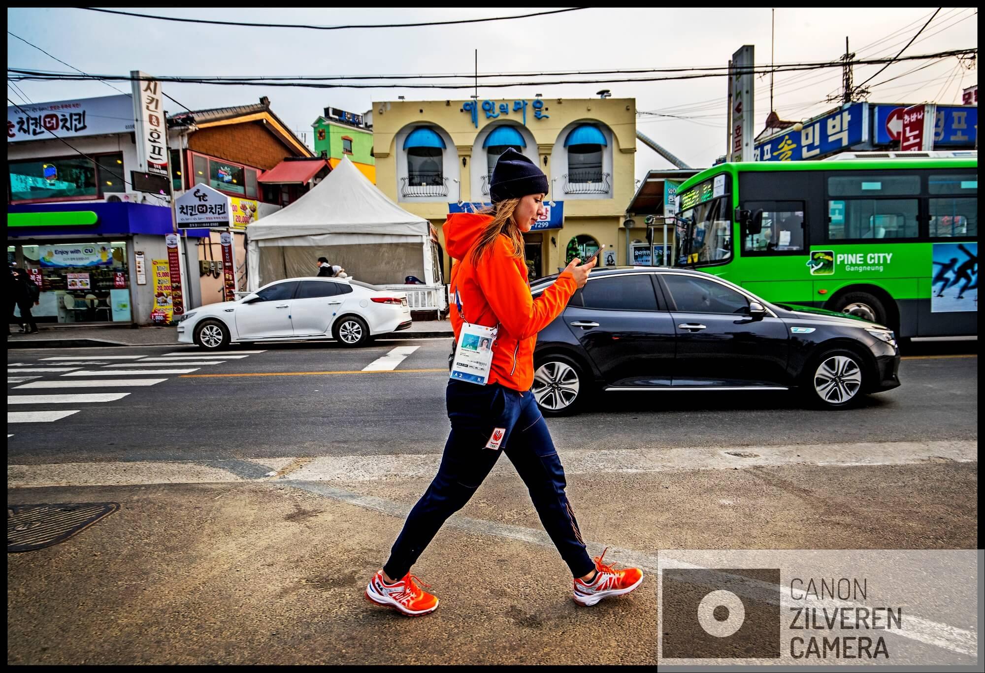 Serie Suzanne Schulting; Van Olympische val tot Sportvrouw van het Jaar. Olympische Winterspelen 2018 Zuid-Korea, Gangneung, 23-02-2018 FOTO 1 Ontspannen loopt Suzanne Schulting door de straten van Gangneung waar het Olympische shorttrack-toernooi wordt gehouden, ondertussen haar Instagram-account checkend.