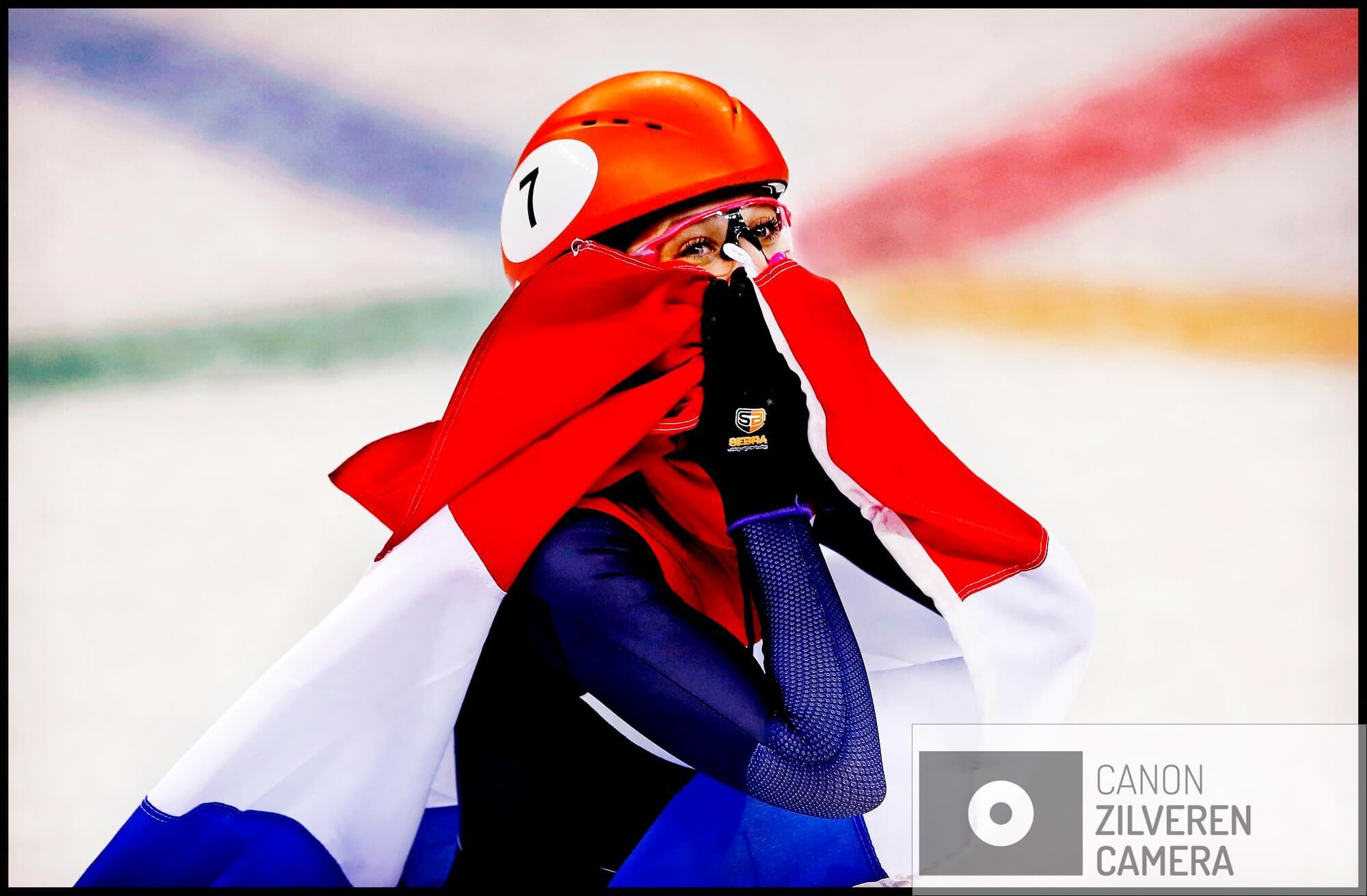 Serie Suzanne Schulting; Van Olympische val tot Sportvrouw van het Jaar. Olympische Winterspelen 2018Zuid-Korea, Gangneung, 22-02-2018FOTO 8Met het logo van de Olympische Spelen als molenwieken rond haar Oranje helm rijdt de verbouwereerde Schulting haar ereronde met de Nederlandse vlag om haar heen gedrapeerd.