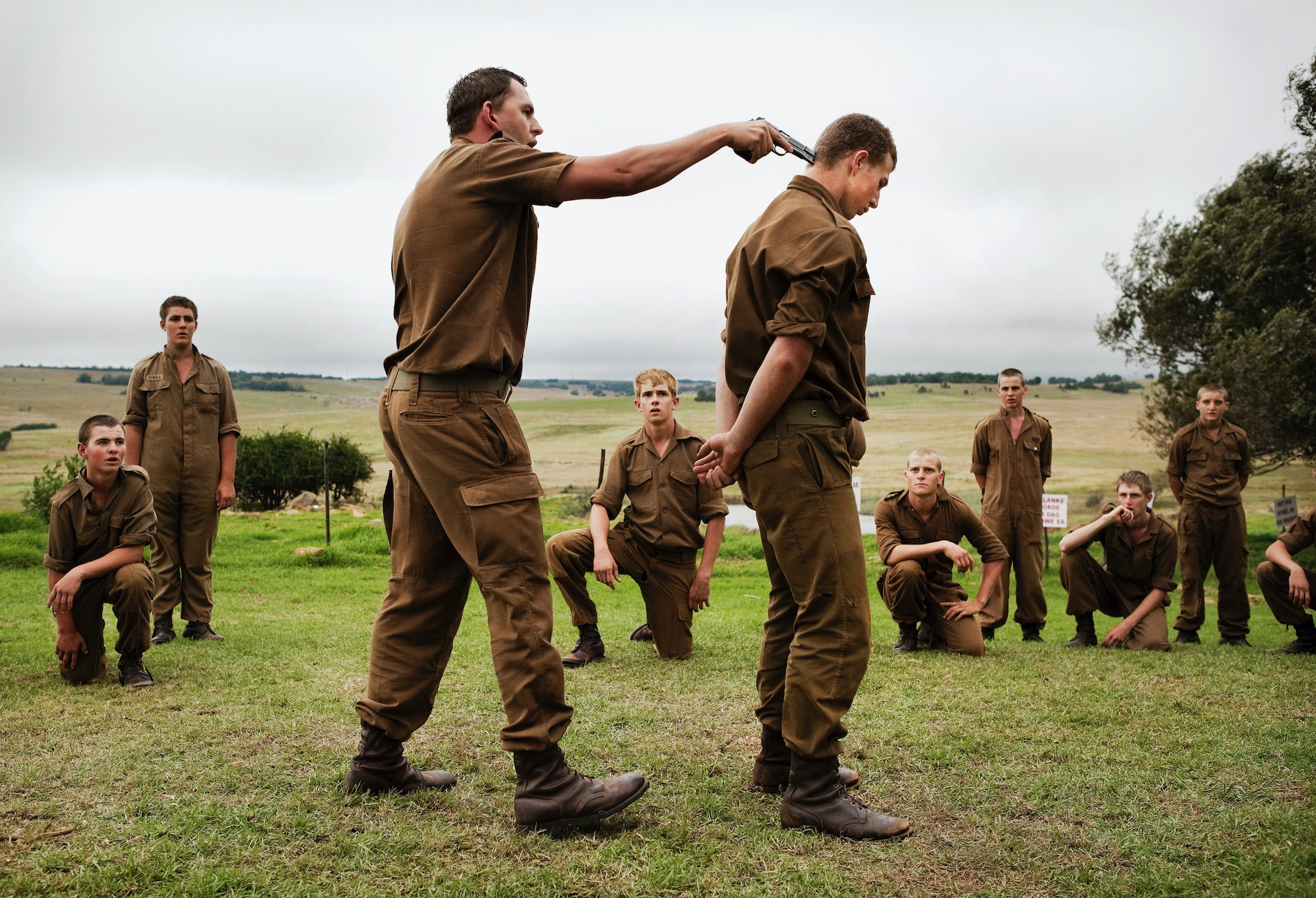 5.  One of the camp leaders points a gun at a boys' heads, during a self defence lesson in the field during the Kommandokorps camp in Carolina, South Africa.  The Kommandokorps organises right wing racist camps during school holidays for young white Afrikaner teenagers, teaching them self-defence and how to combat a perceived black enemy. The group's leader, self-proclaimed 'Colonel' Franz Jooste, served with the South African Defence Force under the old apartheid regime and eschews the vision of a multicultural nation. (2011)