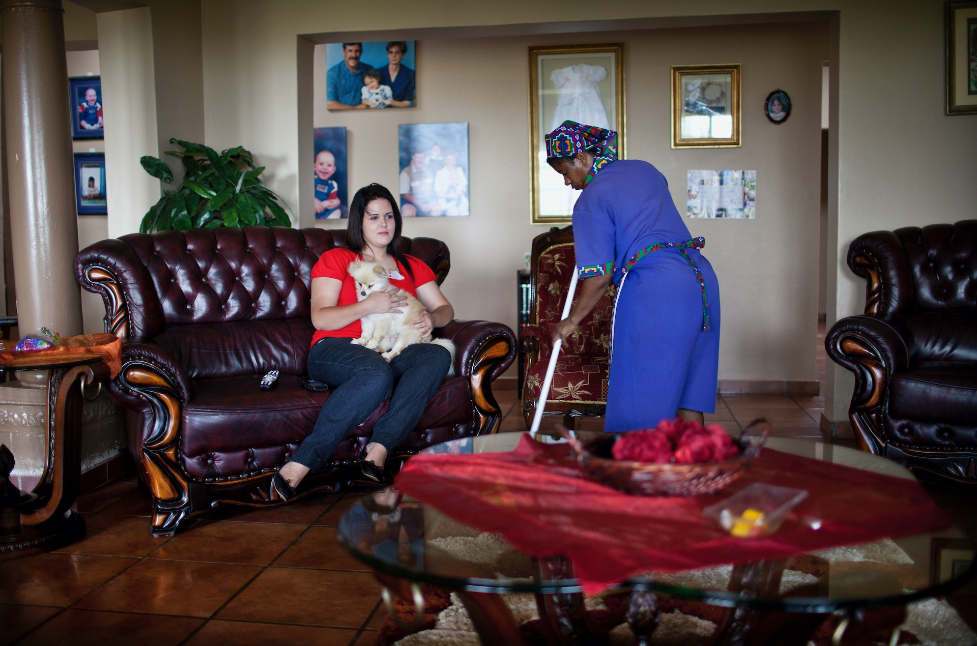 "10.  A domestic worker sweeps the floor beneath Tanya Grobler's (19) feet in Polokwane, South Africa. The family does not know its maid's name, though she has cleaned their home daily for years. They call her by saying ""tsss tsss."" (2012)"