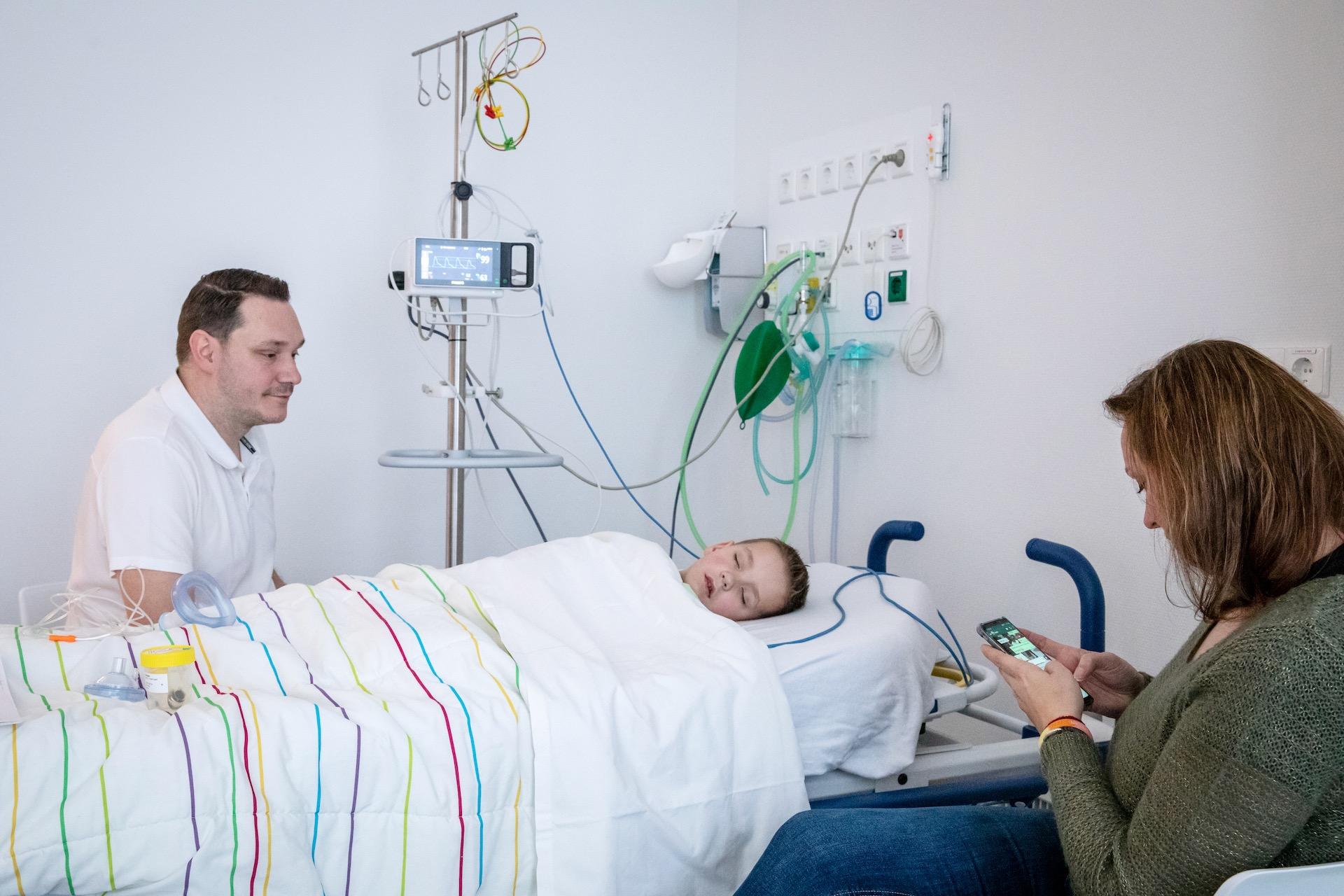 Bjorn slaapt na een operatie. Ze hebben zijn porth a cath verwijderd. Een porth a cath is een onhuidse infuuslijn, waar hij zijn chemo doorheen kreeg. Zijn moeder stuurt de familie een berichtje dat het goed met hem gaat.