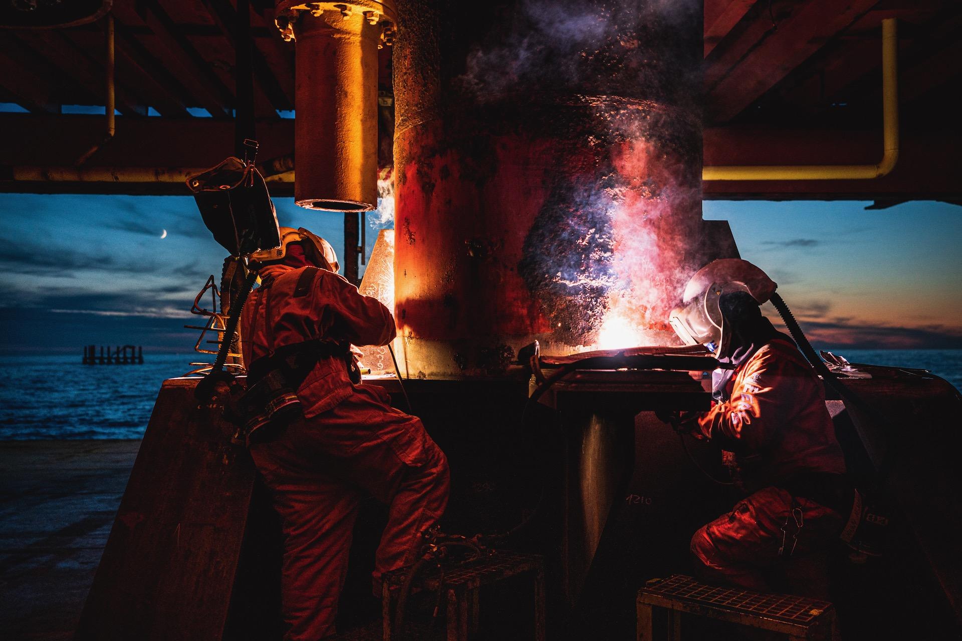 Nederland, Noordzee, 03-08-2019.  Reportage over Kraanschip Thialf. Mannen lassen het boorplatform vast aan het poton waar hij op ligt. Linksachter staan de restanten van het platform nog.  Foto: Siese Veenstra
