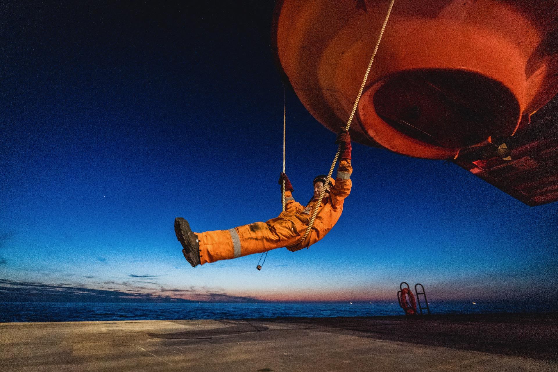 Nederland, Noordzee, 03-08-2019.  Reportage over Kraanschip Thialf. Een man schommelt aan de lifeboat van het boorplatform.  Foto: Siese Veenstra