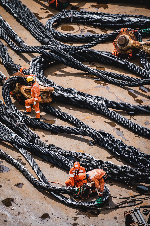 Nederland, Noordzee, 02-08-2019.  Reportage over Kraanschip Thialf. Mannen maken de kabels klaar om straks het boorplatform mee te liften.   Foto: Siese Veenstra