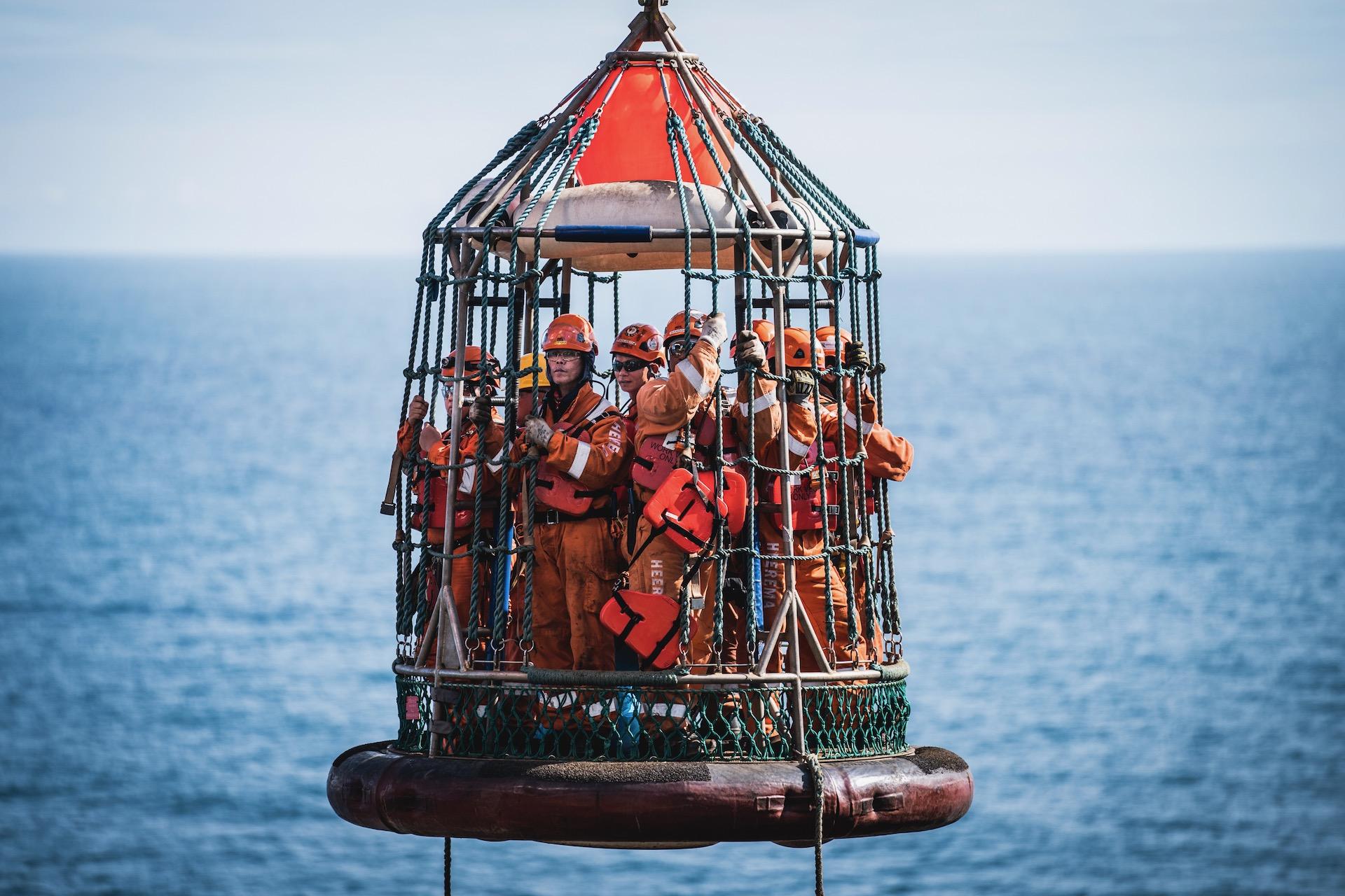 Nederland, Noordzee, 03-08-2019.  Reportage over Kraanschip Thialf. Mannen gaan met de basket van en naar de poton waar het boorplatform nu op staat.  Foto: Siese Veenstra
