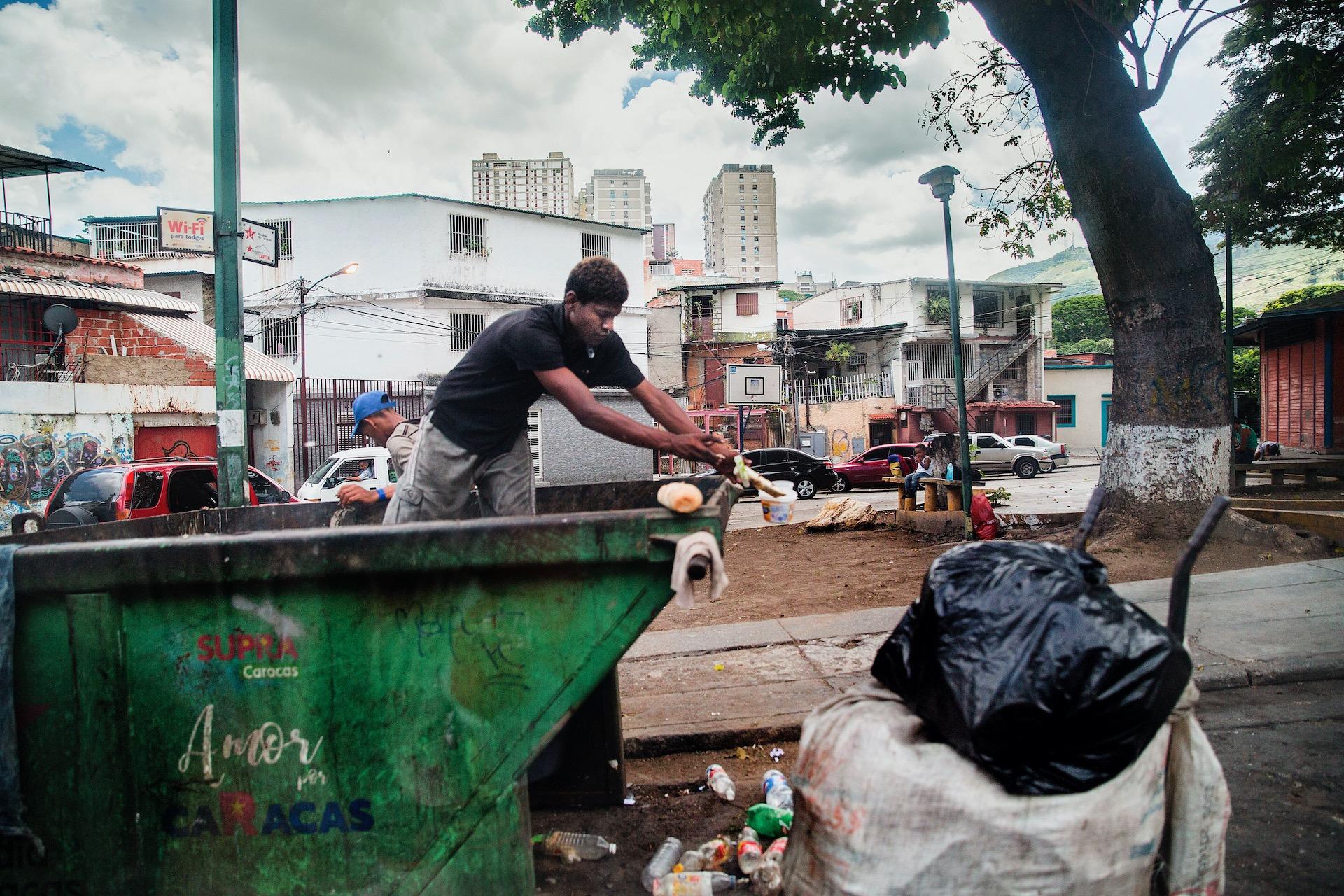 Venezuela CaracasTwee mannen zoeken tussen het vuil of ze iets bruikbaars of te eten kunnen vinden. Vanwege de crisis kunnen veel mensen zich niet voldoende voorzien in hun dagelijkse levensbehoeften. .