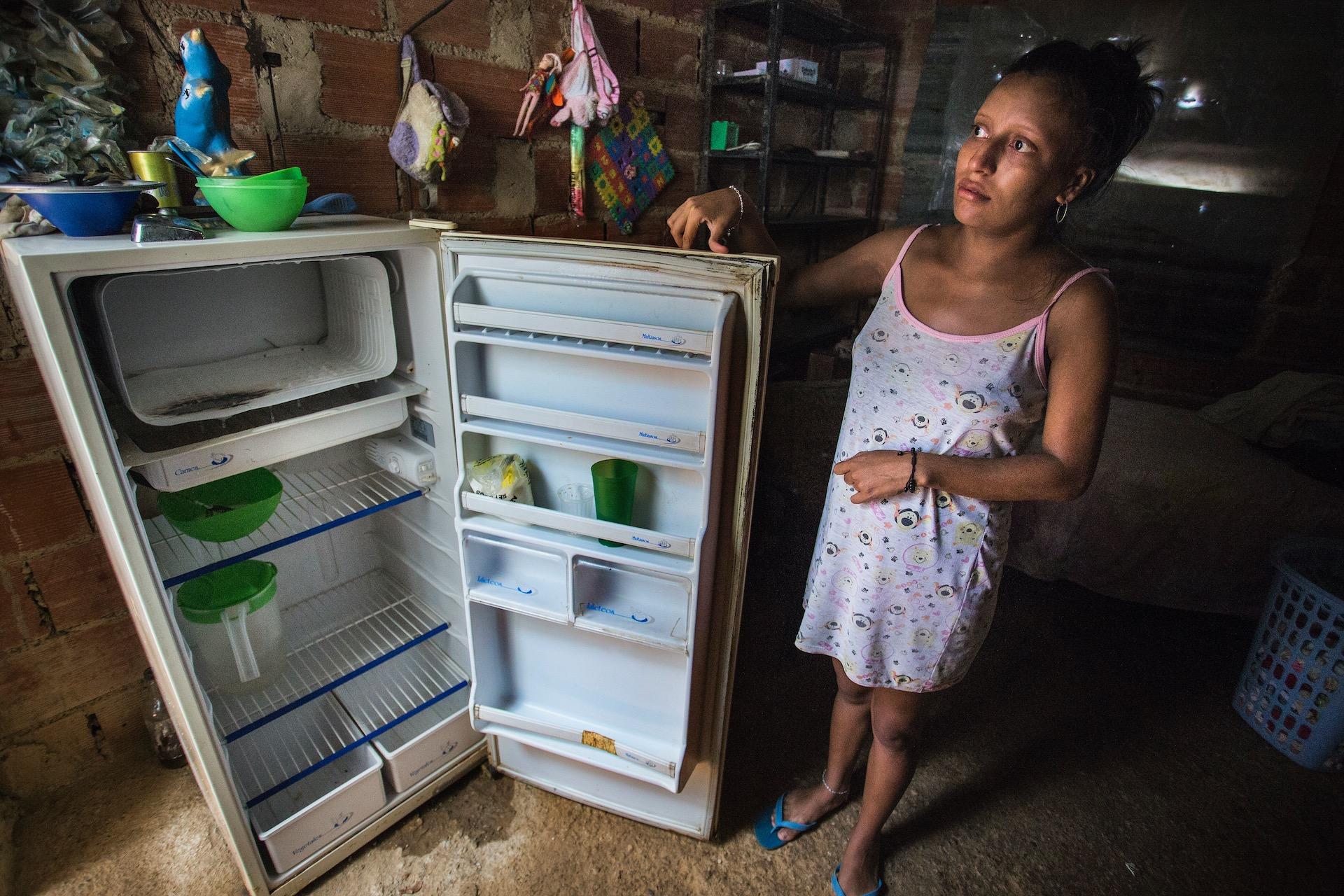 Zwangere vrouw:Imberlin is 23 jaar en zwanger van de tweede. Haar dochtertje is twee jaar. Zij zegt het te redden dankzij hulp van familie en vrienden. Ze is verbaasd als we vragen of we in haar koelkast mogen kijken, want daar zit toch niets in. Haar koelkast staat wel aan maar er zit niets in.In een buitenwijk van Caracas, Mirador de la Lagunita, waar zo'n 380 families wonen. Een plek waar altijd al armere mensen woonden, maar waar tot zo'n vijf jaar geleden gewoon stromend water was. Mensen hadden altijd voldoende eten en medicijnen zoals pijnstillers, maar dat is voor veel van hen nu moeilijk. Veel verscheurde families wonen hier.