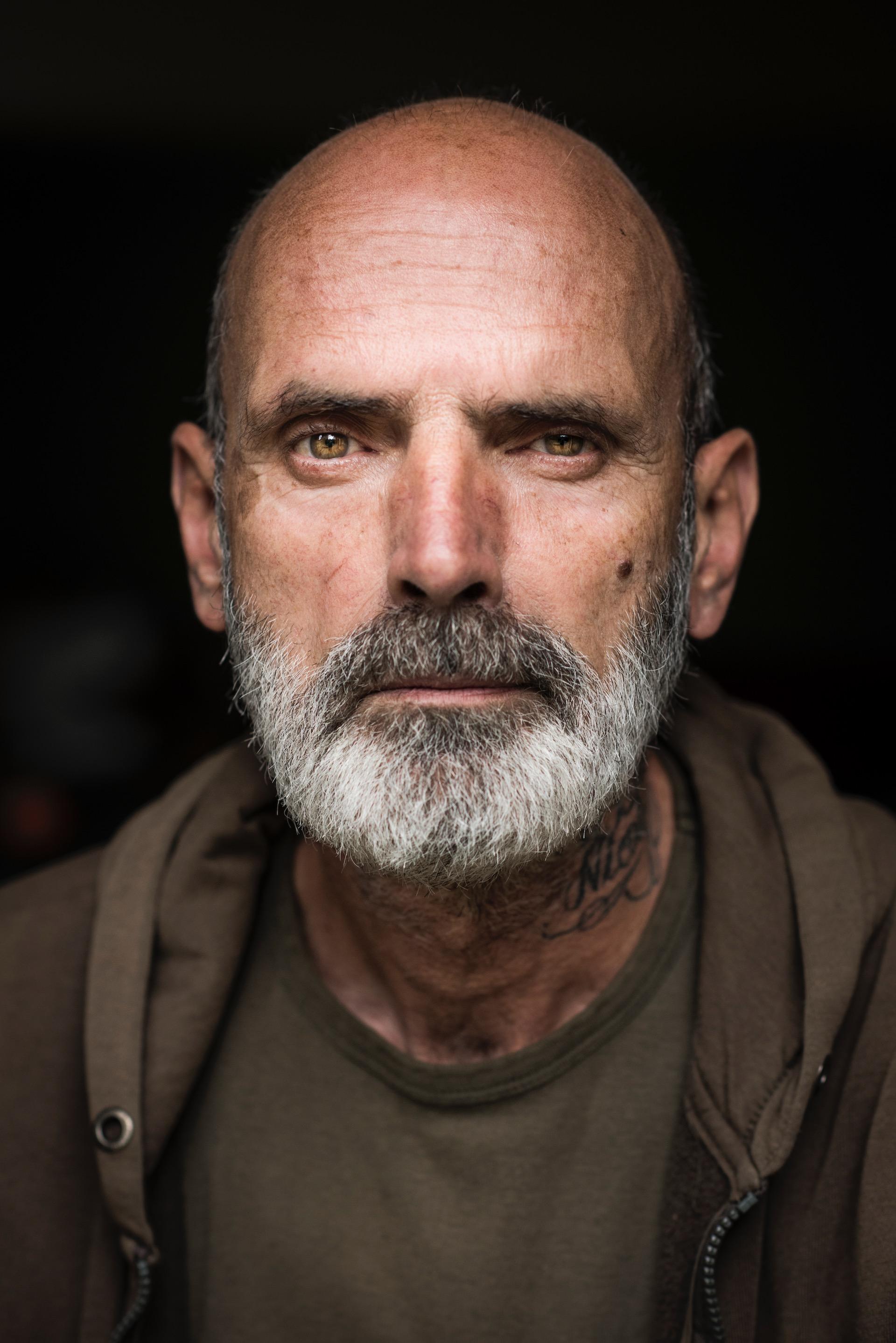 Rob is een veteraan, woonachtig op Thuisbasis Veteranen, een opvanghuis voor militairen die de oorlog niet meer uit hun hoofd krijgen.De veteranen daar kwamen ze in dit opvanghuis terecht in een crisissituatie. Ze deden een zelfmoordpoging, pleegden een geweldsmisdrijf of raakten dakloos. Door defensie voelden ze zich in de steek gelaten. Ze konden nergens meer heen, behalve hier, tussen hun lotgenoten.   Voordat Rob hier kwam, leefde hij in zijn eentje afgezonderd in zijn tentje in de Nederlandse bossen. Soms sliep hij in schuren, in struiken, in verlaten gebouwen. Hij kwam alleen met mensen in aanraking in coffeeshops, waar hij wiet haalde om alles in zichzelf te verdoven - een bestaan dat hij moeiteloos volhield totdat de politie zijn tent in beslag nam, omdat wildkamperen in Nederland nu eenmaal verboden is.   Rob gedraagt zich onopvallend, maar hij is een van de opvallendste mannen in dit huis. Zijn ongeschoren baard en tatoeages geven hem een ruwe uitstraling. Maar hij praat zacht en weloverwogen.    In 1995 werd hij als onderofficier uitgezonden naar Srebrenica. Hij zat in Dutchbat III, het bataljon dat machteloos moest toezien hoe de enclave viel die ze moesten beschermen. Luchtsteun kwam er nooit. Gevolg: een massamoord op achtduizend Moslims – de ergste genocide sinds de Tweede Wereldoorlog in Europa.   Rob weet het allemaal. De martelingen, de executies, de jongensbaby's die werden doodgestoken in de armen van hun moeders. De onmacht die hij voelde toen hij als militair zo slecht werd bewapend dat hij niet kon en mocht doen waarvoor hij was opgeleid. 'Het blijft me eeuwig achtervolgen', zegt hij. 'Ze noemen het ptss, ik noem het een moral injury.'   Hij vecht een 'war at home', oorlog in eigen land. Getraumatiseerde veteranen zijn in Nederland volgens hem veroordeeld tot een strijd. 'Je moet bewijzen dat er wat mis met je is, en dan ook nog eens dat het komt door wat je bij defensie hebt meegemaakt. Omdat veel gasten het faken, zijn ze bij defensie erg wa