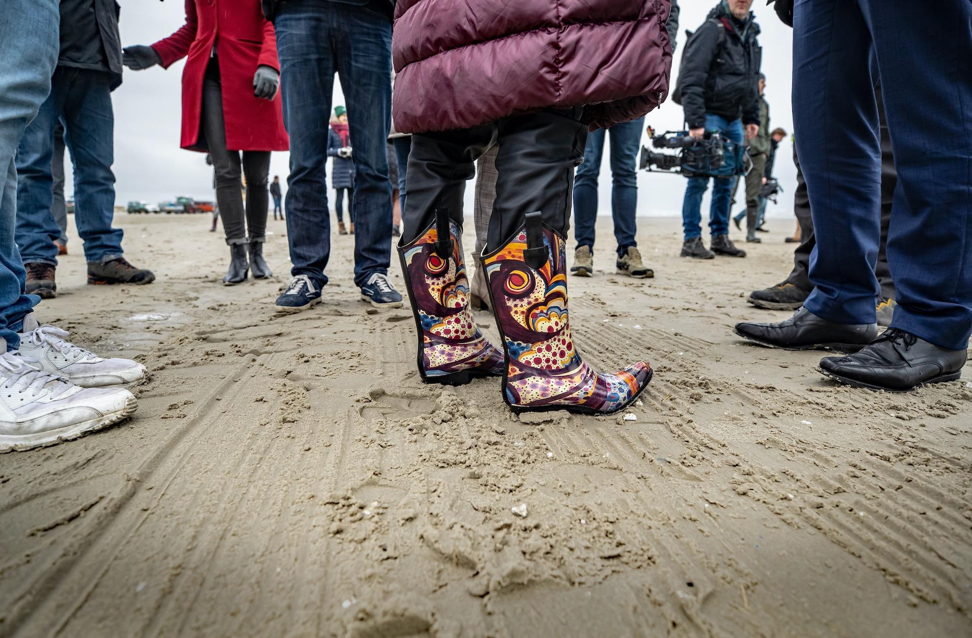 de kleurijke laarzen van de minister  met in het zand met nogal wat plastic  wit op het strandVan Nieuwenhuizen neemt het woord 'ecologische ramp' in de mondMinister Cora van Nieuwenhuizen (Infrastructuur en Waterstaat) brengt donderdag een werkbezoek aan Terschelling. Ze zal zich daar persoonlijk op de hoogte stellen over de gevolgen van de 290 containers die vorige week zijn verloren door het containerschip MSC Zoe bij de Waddeneilanden. foto 6