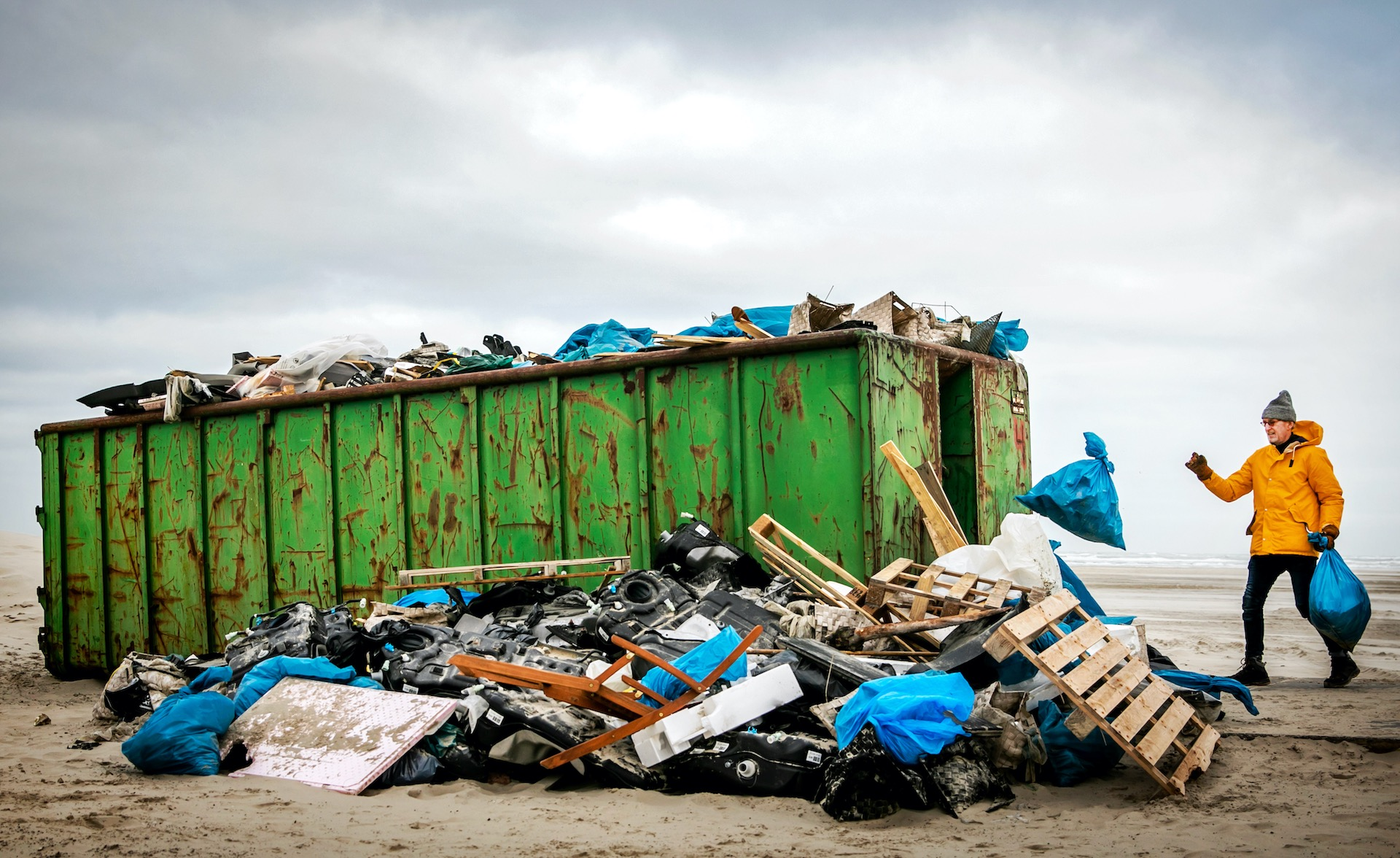 TERSCHELLING - Een man brengt afval naar een container na een opruimactie op de stranden van Terschelling.