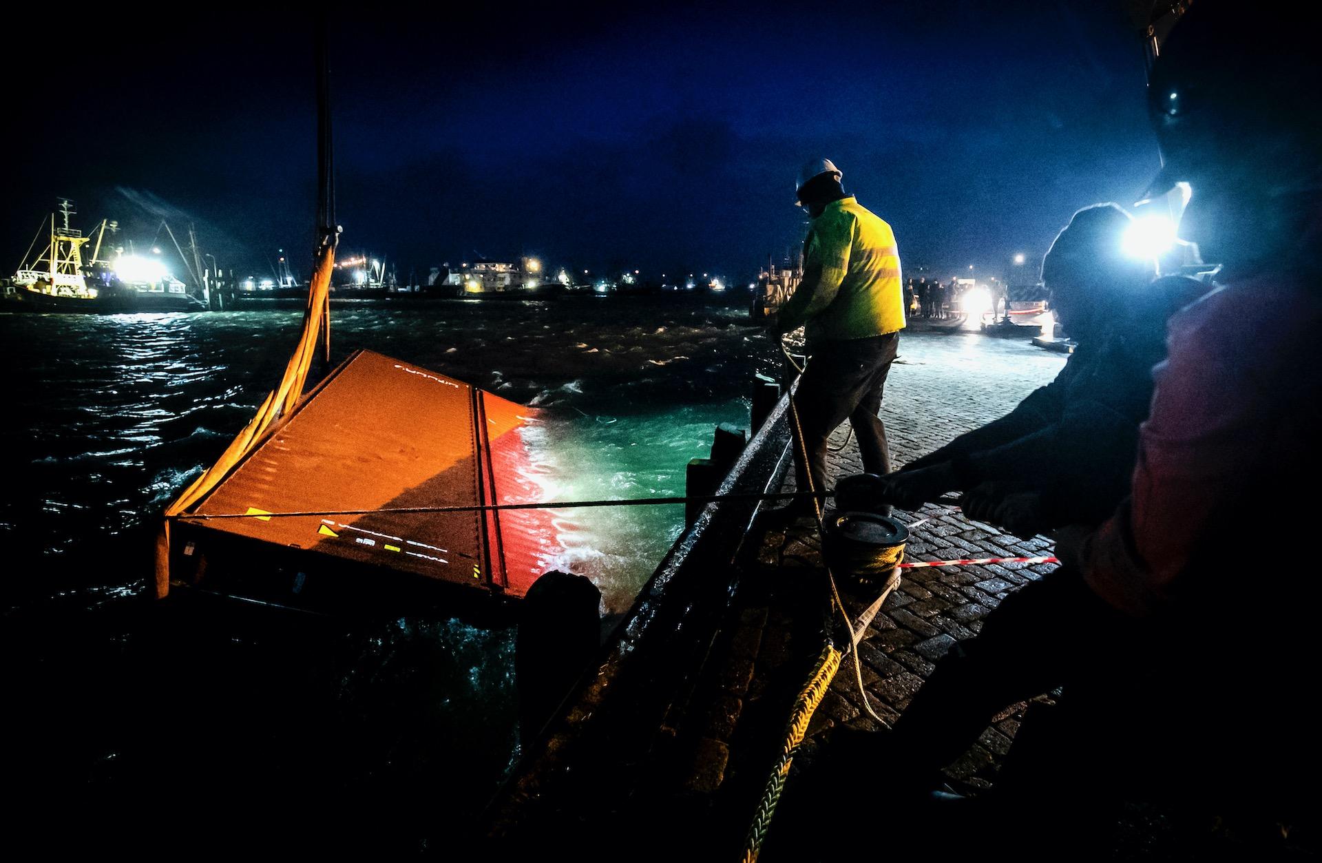LAUWERSOOG - Een sleepboot brengt twee overboord geslagen containers van het schip MSC Zoe de haven binnen.